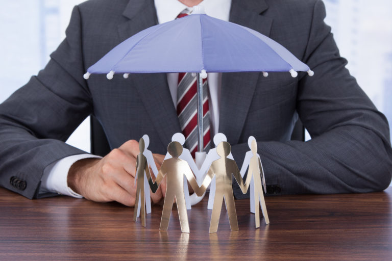 Midsection of businessman sheltering paper people with umbrella at desk